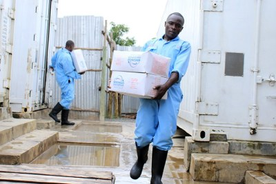 Workers carry tilapia sourced from China at a fish depot in Kisumu.