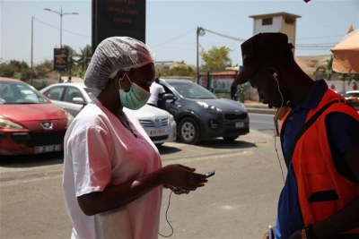 Penda Kande refills her mobile money account with an agent in Senegal's capital, Dakar on March 27, 2020.