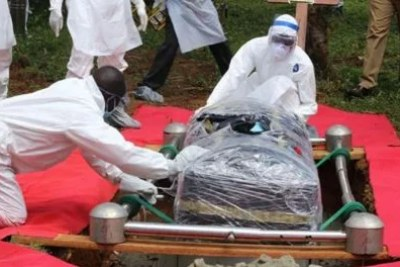 Health officials in protective clothes bury the body of Anthony Waswa on May 19.