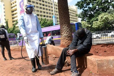 An official from the Nairobi Health Department disinfects a street in fight against the new coronavirus.