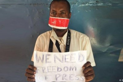 A Tanzanian holding a sign reading
