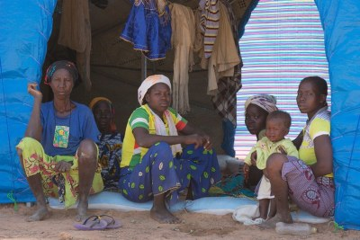 Members of a family who fled conflict at their shelter in the Pissila camp for internally displaced persons in Burkina Faso.