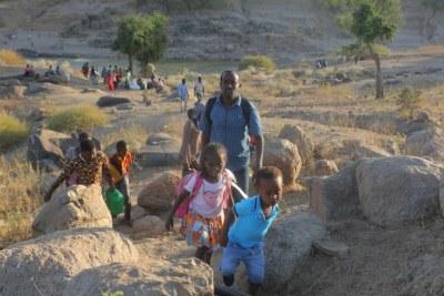 Ethiopian refugees walk through rocky terrain to reach Hamdayet, Sudan.