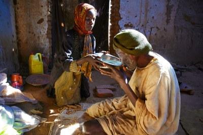 Une fillette de sept ans donne de l'eau à son grand-père pendant qu'il prie dans un camp pour personnes déplacées au Darfour, au Soudan.